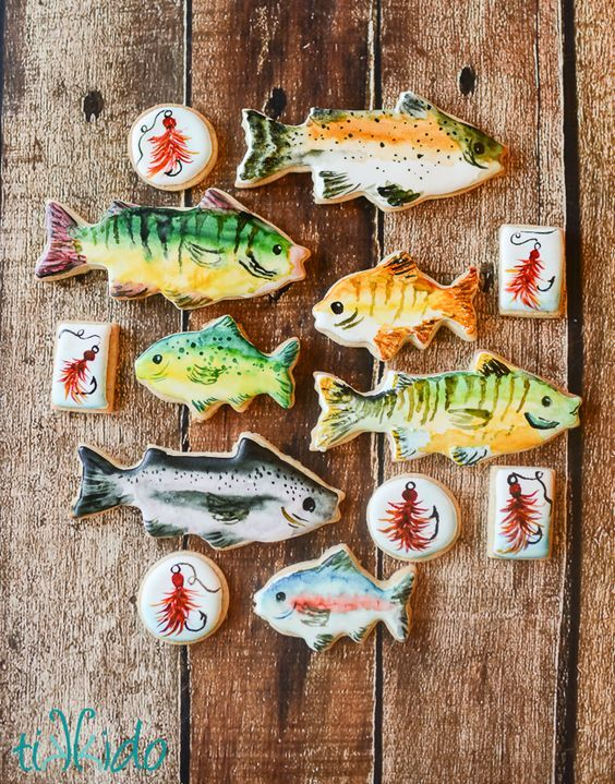 watercolor style painted fish and lure sugar cookies for a fishing themed baby shower.