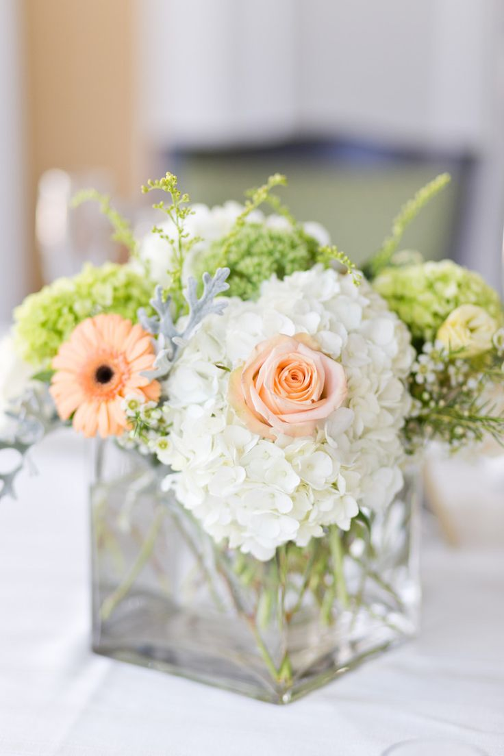 Low centerpieces included white hydrangeas, peach daisies and roses, and verdure in modern cube vases. #FloralCenterpiece Photography: Cassi Claire Photography. Read More: http://www.insideweddings.com/weddings/casually-chic-country-club-wedding-in-new-york-with-pastel-details/662/