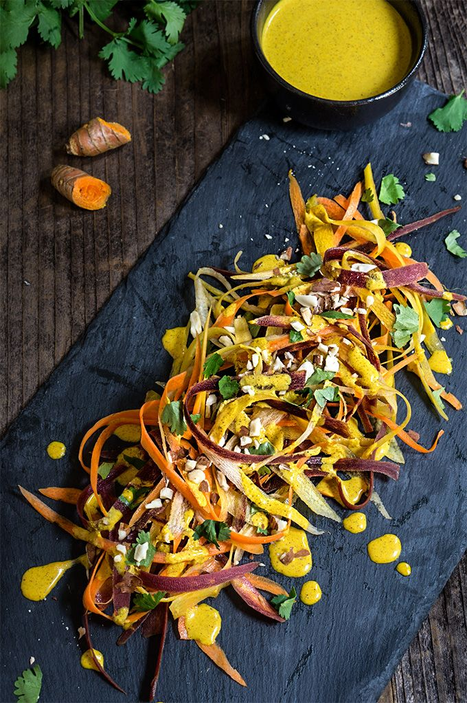 Carrot almond salad - ribbons of rainbow carrots, doused in creamy, turmeric coconut dressing, topped with toasted almonds and fresh cilantro - an explosion of exotic flavors that will surely tantalize your taste buds!