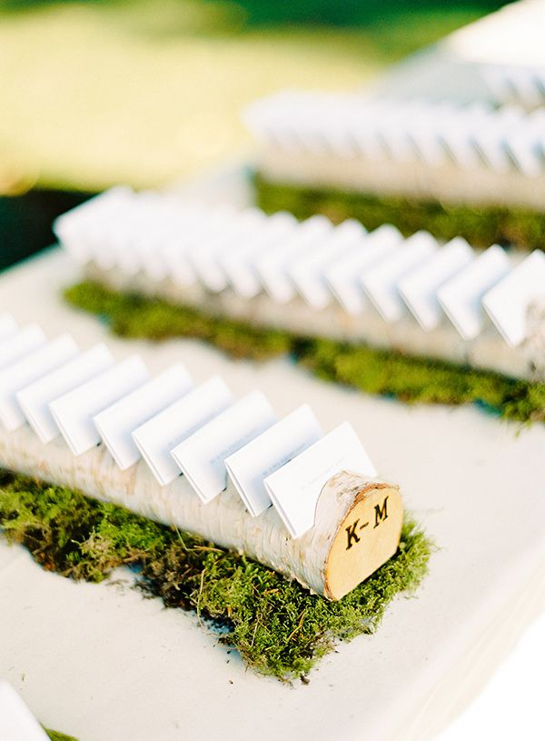 Unique escort card display with wooden logs. love the detail of the monogram on the ends