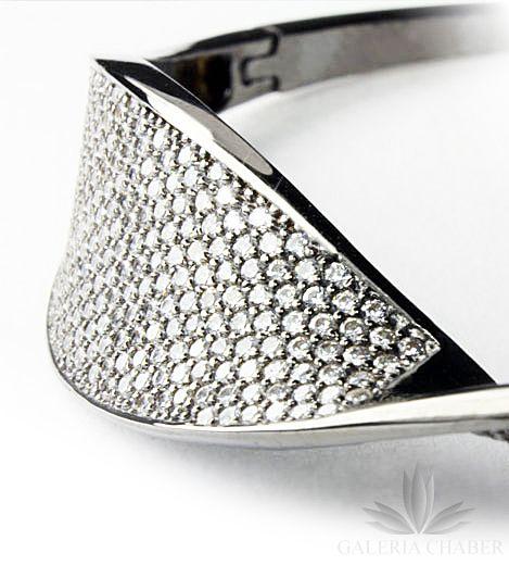Ciekawa bransoletka wykonana ze srebra próby 925, oksydowana. Nowoczesna forma. Wyrób wysadzany białymi Cyrkoniami, kontrastującymi z ciemnym tłem. Bransoletka sztywna, o średnicy około 6 cm wewnątrz. Zapięcie szufladkowe, zabezpieczone dodatkowo tzw.