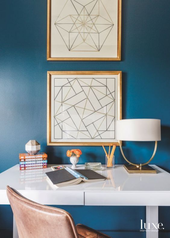 Home office with blue walls and gold accents