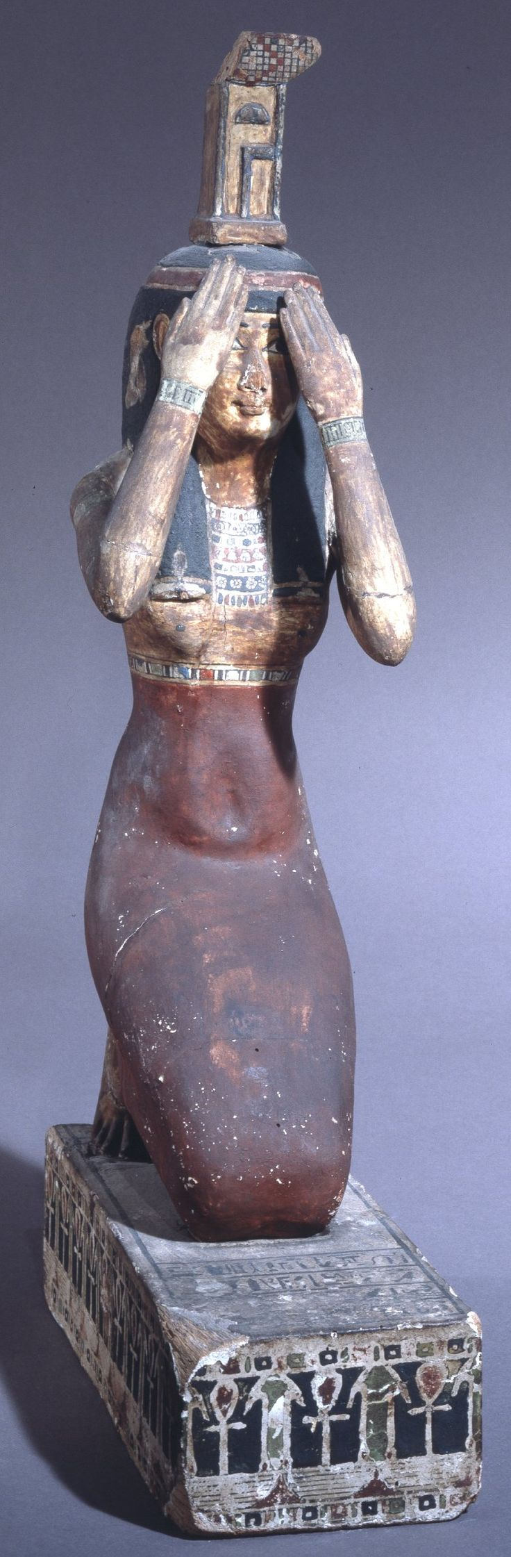Wooden figure of Nephthys with the hands raised to the face in mourning. | The…
