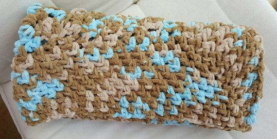 A beautiful, snugly, hand crocheted baby blanket made in baby blue and pale and medium shades of brown. Made from a cosy fleece bulky yarn, this blanket is thick and warm. Perfect for baby boy in the winter months.  Measuring ~87cm (36 inches) square this blanket is perfect size to keep baby or toddler cosy in pram, car seat, cot or Moses basket.  The soft fleecy yarn is 100% polyester making it machine washable and easy to care for.  A perfect new baby boy gift or a baby shower present…