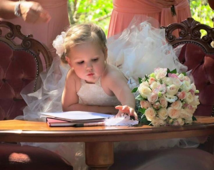 A gorgeous moment captured of our flower girl laying beside the bride's flowers.