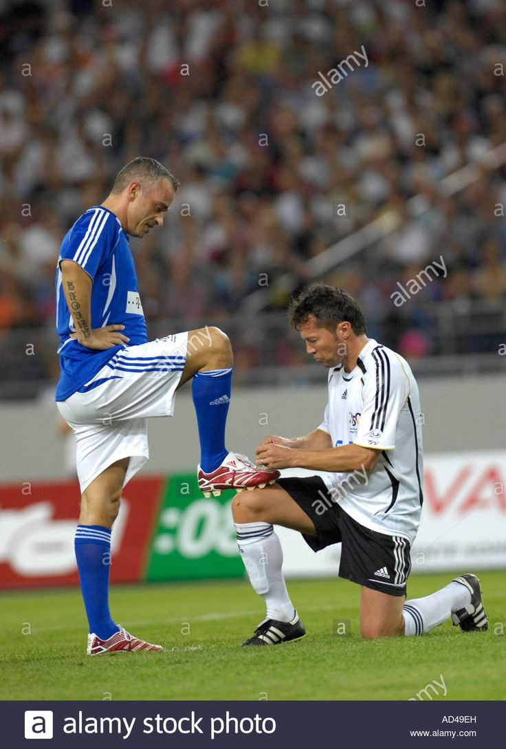 Lothar Matthaeus Ger polishes shoes of Eros Ramazzotti at 25 year anniversary match of 1982 World Cup final of Germany VS Italy