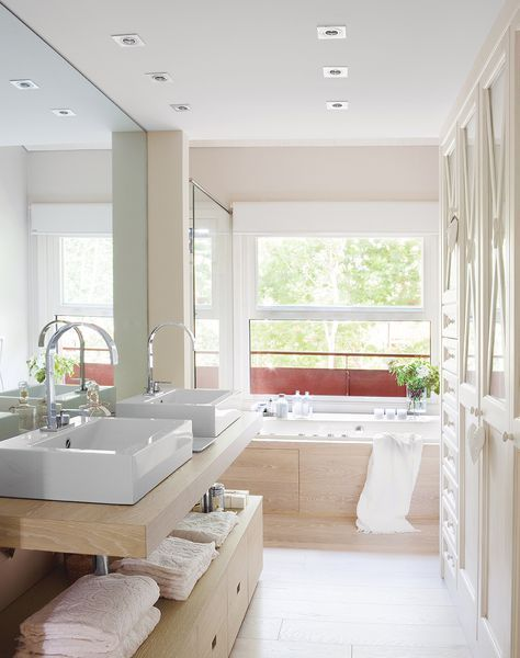 Baño con vestidor, doble lavabo y bañera, con suelos y revestimiento de madera clara y blanco_305133