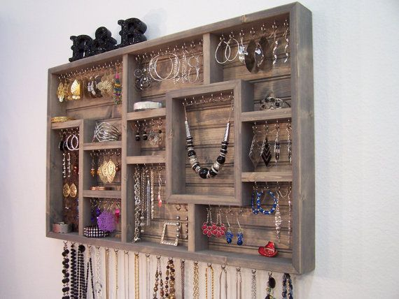 Organize your jewelry using this display case. This earring holder is stained grey in color and made of pine wood. This jewelry organizer