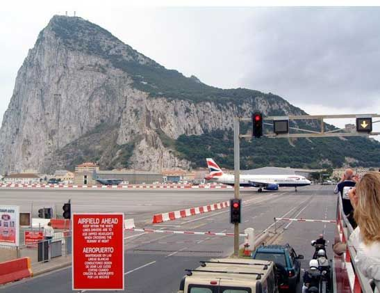 Road crossing Gibraltar Airport.   Red traffic light stops the traffic while an aircraft takes off :-)