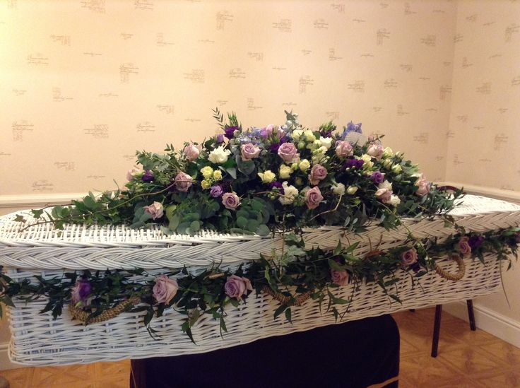 Funeral Flowers. white wicker coffin with a beautiful garland of  lilac memory lane roses, deep purple Lisianthus and soft ruscus. Coffin flower garland, lilac coffin spray. beautiful funeral flowers. www.thefloralartstudio.co.uk