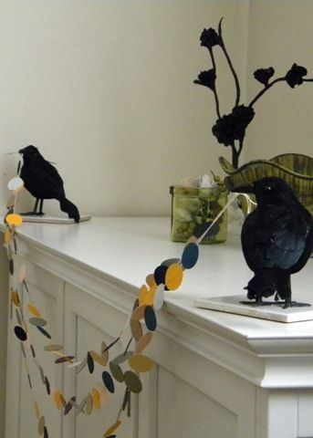 Dollar Store crows holding up a Halloween garland. @carolyn is a genius!