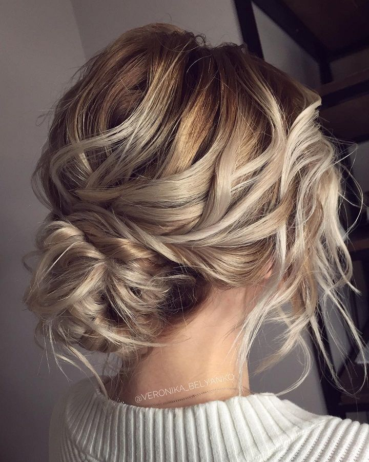 A beautiful textured wedding up style with a low messy bun