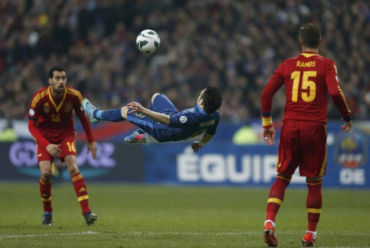 Mathieu Valbuena kicks the ball between Spain's Sergio Busquets and Spain's Sergio Ramos during their 2014 World Cup qualifying soccer match at the Stade de France stadium in Saint-Denis, near Paris, March 26, 2013. REUTERS/Benoit Tessier