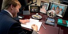 Koning Willem-Alexander zet in zijn werkkamer in Paleis Noordeinde zijn handtekening onder een aantal wetten