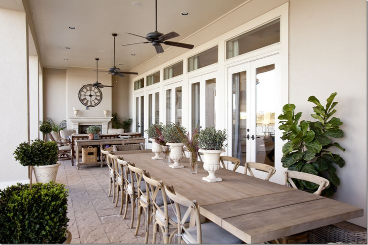 This covered porch has a huge table that seats 14. On the other end is a seating area and fireplace