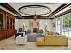 mansion living room white modern leather chair mustard yellow L shaped sofa ornate black and white ceiling circular moldings design