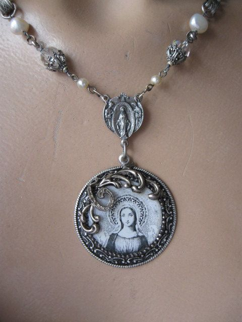 A graceful, ancient Madonna rests under resin in a hand-fashioned bezel beneath a repurposed rosary center. Small faux pearl rosary beads connect to capped vintage crystals, large freshwater pearls, and ornately engraved silver plated book chain.    Adjusts 17 to 19 (if you would like the length adjusted a bit, just let me know. I can add or subtract a link or two).