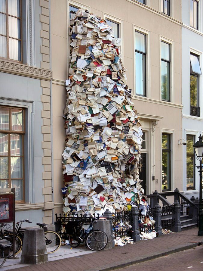 Hundreds of books appear to be pouring out of a museum's window in The Hague, The Netherlands. Alicia Martin,   http://www.frameweb.com/news/biografias-vi-by-alicia-martin