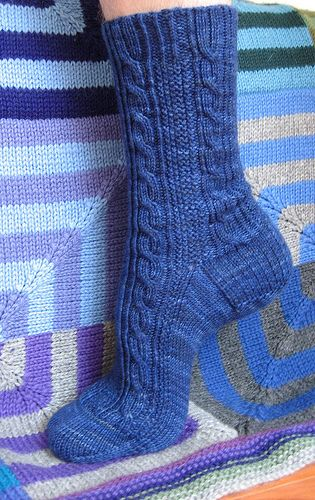 The sock features a moss stitch panel that is flanked by two cables running down either side with a twisted stitch detail flowing out of the cuff ribbing.