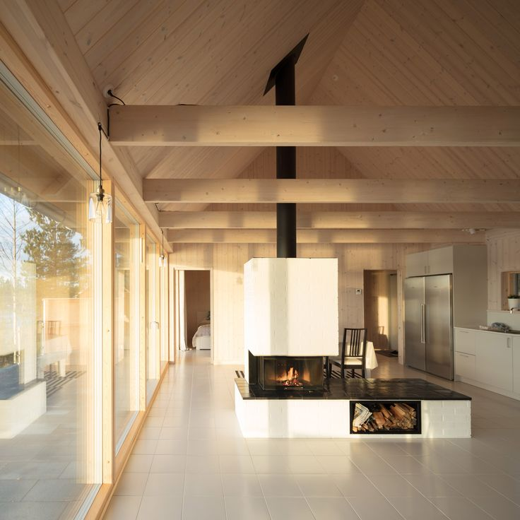 A painted-brick fireplace separates areas for living and dining at this summer house designed by London-based architect Tina Bergman for a plot looking out towards the sea on Sweden's east coast.
