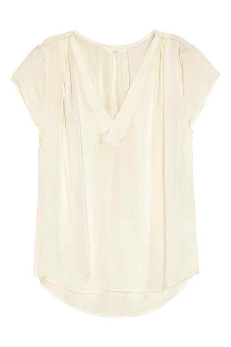 Blusa de satén cuello de pico: Blusa de satén de manga corta con cuello de pico, pliegues en los hombros y en la nuca, y parte inferior redondeada con parte trasera ligeramente más larga.