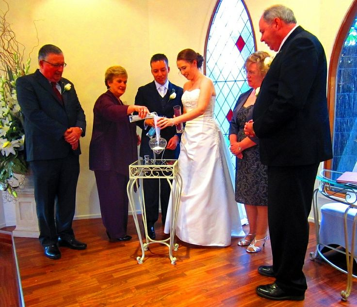 A bride and groom perform a sand ceremony, together with their parents at Bram Leigh chapel
