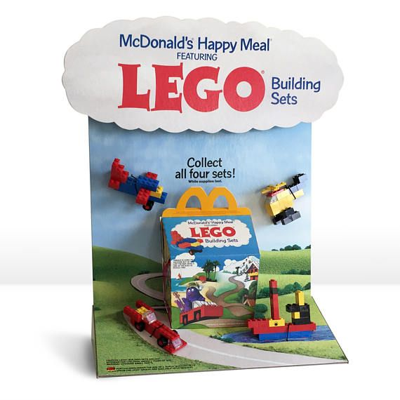 A fantastic 1986 McDonalds Happy Meals Lego Building Sets advertising counter display with Lego toys attached. This unique and very hard to find vintage restaurant display was found on the counters in McDonalds Restaurants and showcased the four Lego Building sets found in the Happy Meals. The display is in excellent to near mint condition. Cardboard pieces show very little wear except very minor wear on corners. Colors are bright with no tears, and display is complete.  Size is…