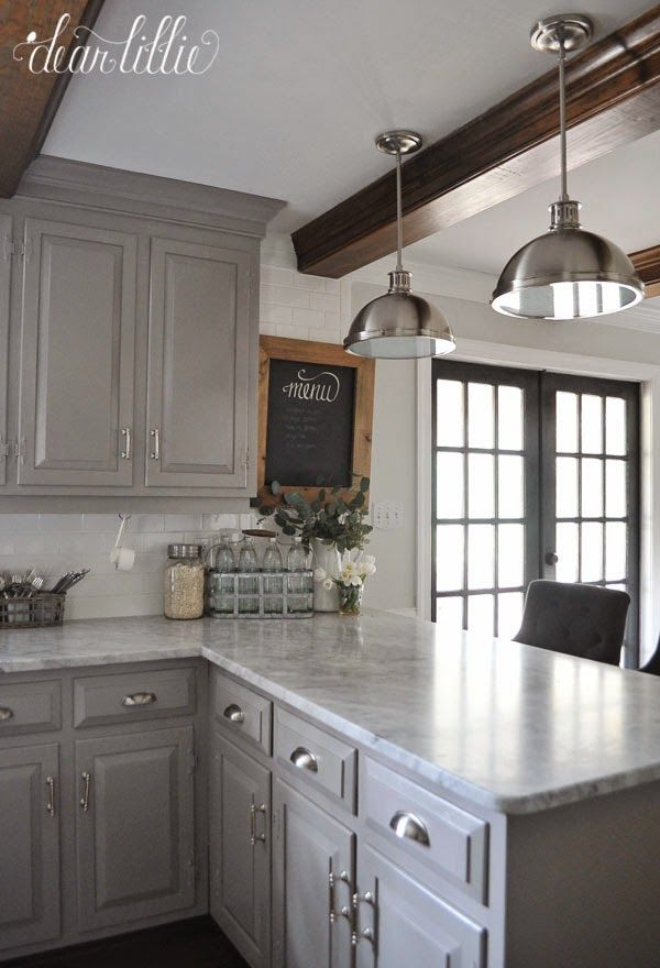 Love the light gray cabs and counter tops, white subway tiles. Love the dark french doors with white trim .