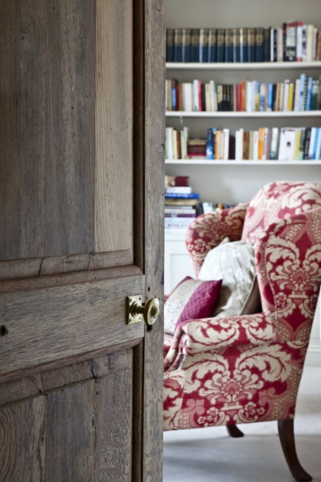 Cozy room with books and an old patterned, red-white armchair.