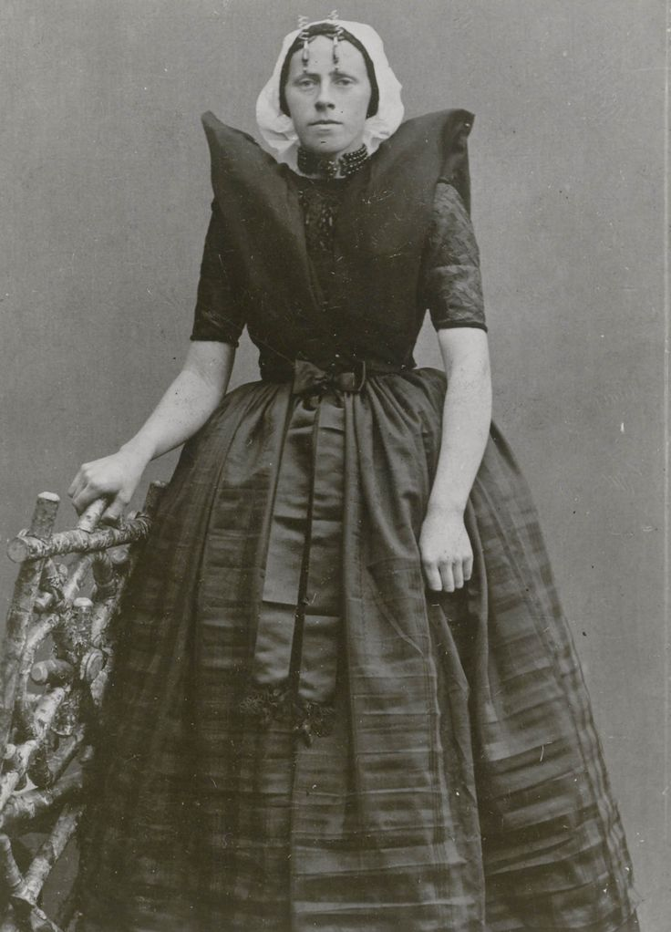 Suzanna Hofman in Axelse streekdracht. Suzanna is gekleed in haar zondagse dracht. Ze is in de rouw. Over de zwarte ondermuts met het oorijzer draagt ze een 'ronde muts' of 'hernhutter' (type muts), welke gedragen wordt door meisjes tussen het 7e en 14e levensjaar, en soms door volwassen vrouwen. Aan de 'krullen' (oorijzeruiteinden) draagt ze 'rouwklokken' (pegelvormige oorijzerhangers). ca 1900 #Zeeland #Axel