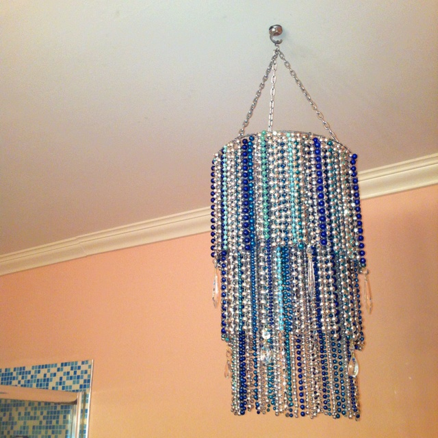 "My first Mardi Gras bead craft - a three ring chandelier. I wired the beads onto a 12"" metal wire wreath frame that I spray painted silver to match. I added a few crystals I had as well using fishing line. Looks great in our bathroom above the tub!"
