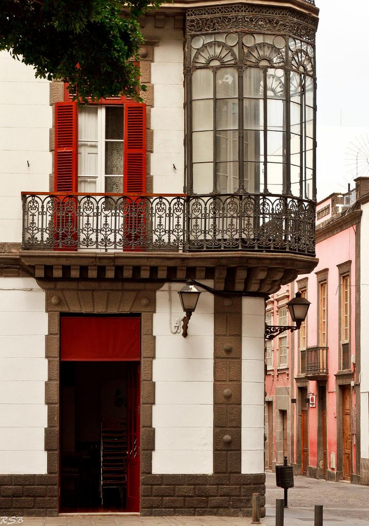 Canary Island, Spain. I LOVE the iron work. The balcony, the windows, the red shutters, love it all.