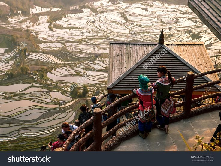 Tourists and two young girls in Chinese Women ethnic National costumes Hani minority observe the delightful Sunset on the Review site. Rice terraces. Ksindze, Kunming, China,  22 of February, 2013