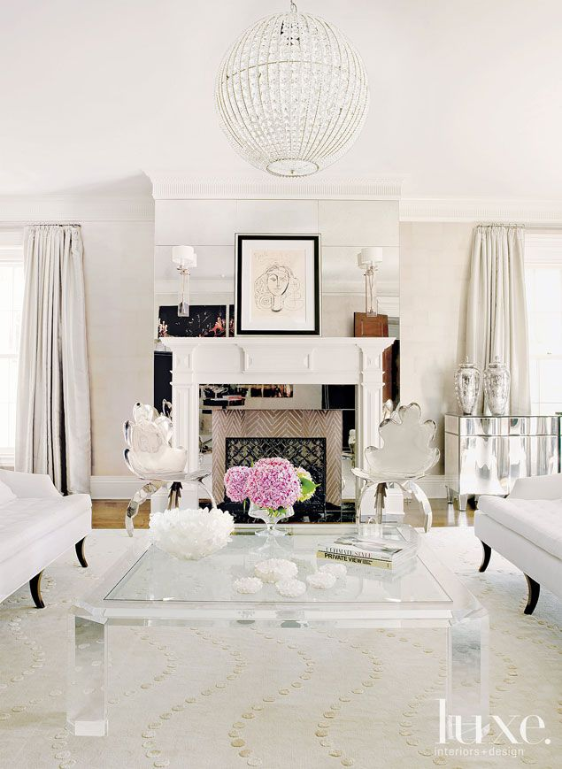 This white Greenwich living room blends modern glamour with classic sophistication. A reflective fireplace mantle and polished nickel chairs offers an eclectic edge to posh interiors.