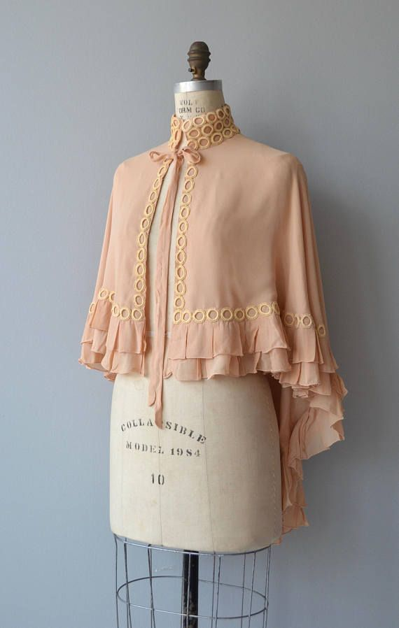Vintage 1930s layered peach silk capelet, longer in the back with laced applique, ruffled hem, high collar and tie ribbon. --- M E A S U R E M E N T S --- fits like: fits small/medium/large shoulder: open bust: free waist: free length: 19 at the front, 32 from back of neck to hem brand/maker: n/a condition: excellent ➸ More tops & sweaters https://www.etsy.com/shop/DearGoldenVintage?section_id=5800171 ➸ Visit the shop http://www.D...