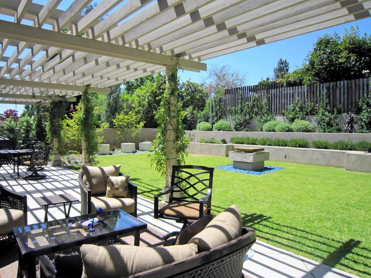 A picturesque pergola provides shade for a lovely outdoor seating area that looks out onto an elevated garden, which makes the most of a small backyard.