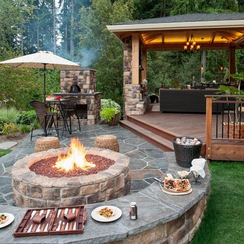 I love the way the gas fire pit is set on the natural stone patio with the covered outdoor kitchen and outdoor fireplace. Really nicely done!
