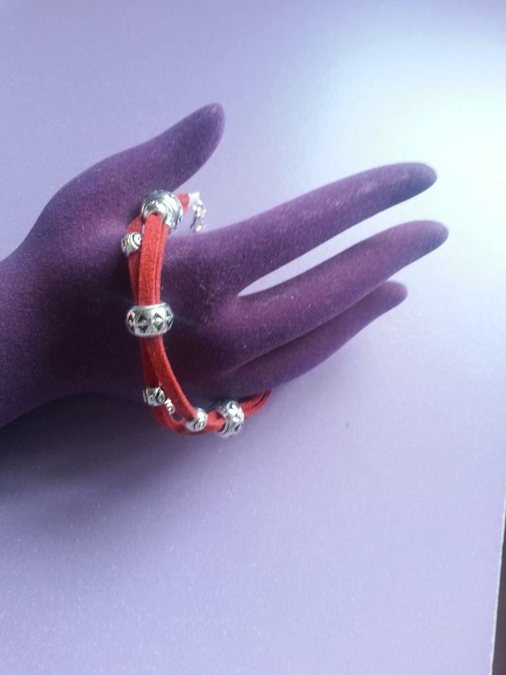 Pulsera de ante roja con pequeños adornos de plata y cierre de pinza. Perfecta para cualquier ocasión.