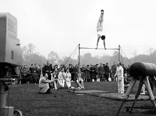 The British Olympic Team of Gymnasts practise on the high bar in Hyde Park.