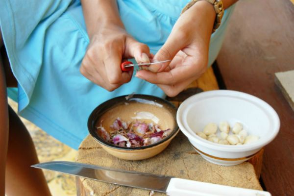 "How to Peel Garlic Faster:  ""Take the back of your knife in the base of your hand, and smash the keel with your palm. Use a little bit of elbow grease so that the skin peels off after one hit. [You will need to repeat this on the whole clove to crack it]. Then you turn it to the side and cut off the wooden tip. Now you have your peeled clove of garlic. Everything has essential oils to it-lime, lemon, lemongrass, celery, coriander seeds-so popping garlic like that and then cooking ..."""