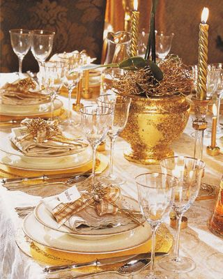A golden Christmas table setting shimmering and glistening in the mood for a wonderful happy day. JH