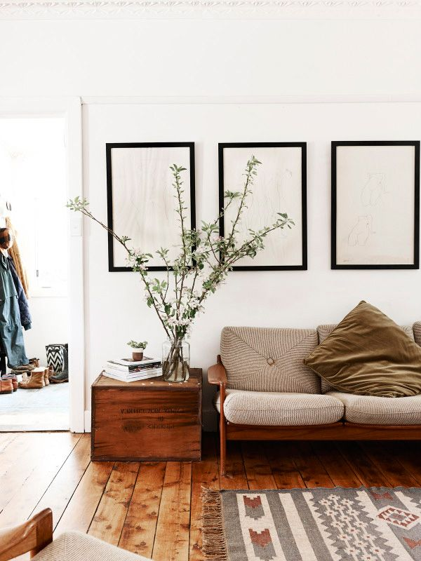 Great wood floor, The wood box as side table gives the room a little industrial touch. The idea to use empty frames looks good and modern in there.