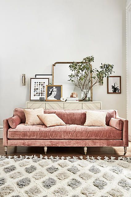 Layered frames and mirrors above the couch. Living room. Eclectic design.