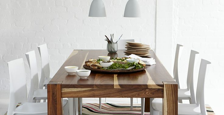 Long feature wooden table, white plastic chairs, white down lights