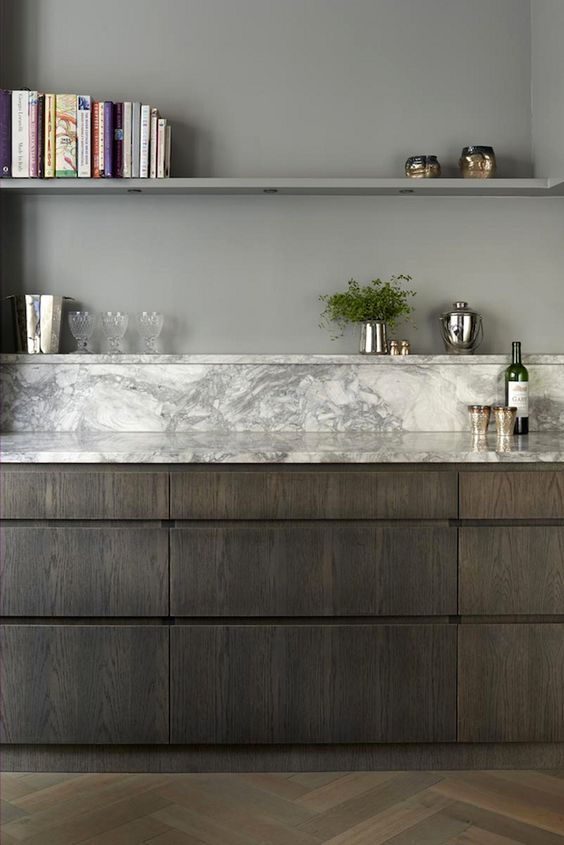 marble counter transitioning to backsplash and shelving, dark cabinetry with vertical grain, herringbone floors: