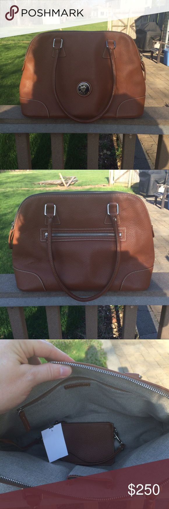 """Dooney & Bourke leather satchel bag & wristlet NWT Beautiful light brown or dark tan all weather domed satchel w/matching wristlet that had a detachable chain.  One zippered pocket on the outside, one zippered pocket on the inside, and one small open pocket on the inside.  The satchel is approx. 10-1/2"""" H x 16-1/2"""" W x 5-1/2"""" D with a 8-1/2"""" strap drop.  It zippers closed across the top.  The detachable wristlet is approx 4"""" H x 5-3/4"""" W.  Little metal feet on the bottom.  Very nice. Sold on…"""