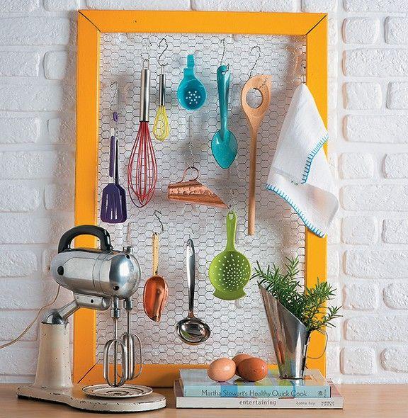 """Uma infinidade de utensílios cabe no porta-treco improvisado com tela de galinheiro e moldura. Para os ganchinhos, arames em formato de """"s"""". Pintado com uma cor bem viva, como este feito pela loja Acervo à Venda, o quadro vira uma alegria na cozinha"""
