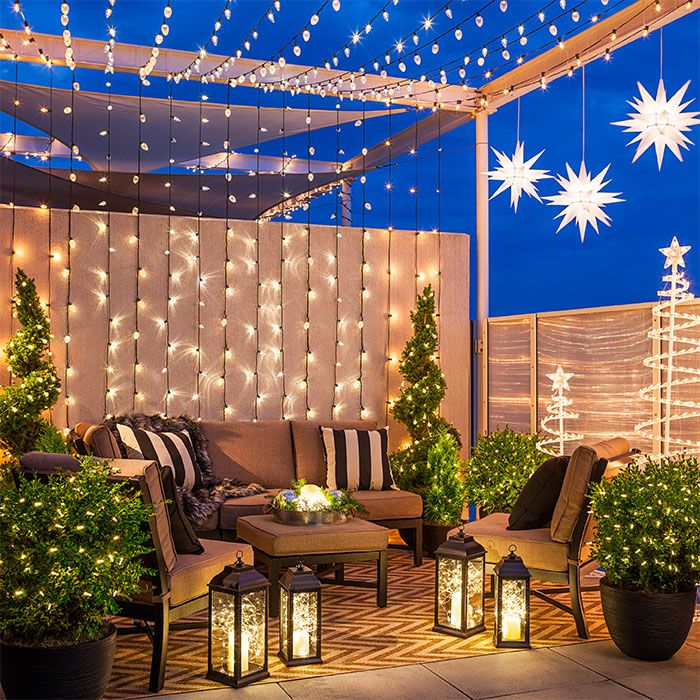 Outdoor space with Christmas string lights attached to beams and a wall, with lighted stars, lanterns and string lights in plants.