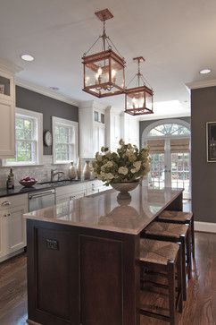 Oh my gosh. Love the marble subway tile backsplash, the white cabinets, the dark wood island with the light stone countertop, the floral arrangement, the wicker stools, and most of all, those gorgeous copper pendants!