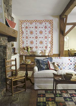Show off your favorite quilts through out the house. Here, an 1880s appliqué quilt hangs on the wall. Another adds a shot of color draped over a white sofa.
